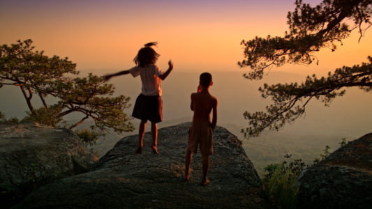 wannasa-wintawong-as-ja-and-tanapol-kamkunkam-as-boy-on-the-clifftop-at-sunset-in-the-forest